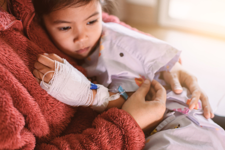 Sick asian little child girl who have IV solution bandaged hugging her mother with love in the hospital Standard-Bild