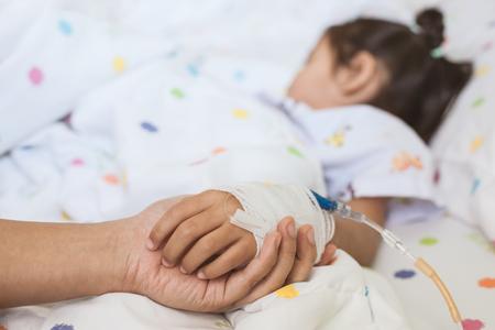 Main de mère tenant la main de sa fille malade qui a une solution IV bandée d'amour et de soins pendant qu'elle dort sur le lit à l'hôpital