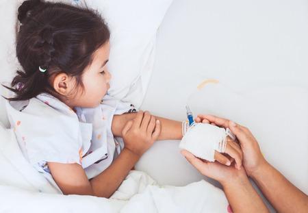 Madre que sostiene la mano de la hija enferma que tiene una solución IV vendada con amor y cuidado mientras duerme en la cama en el hospital