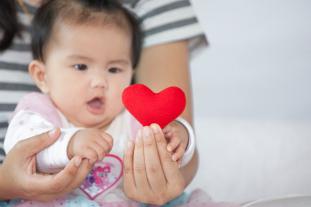 Cute asian baby girl  playing with her mother and try to catch red heart on mother hand with fun and curious Banque d'images