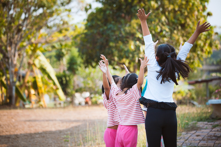 Asian children raise hands and playing together with fun in the park Stock Photo