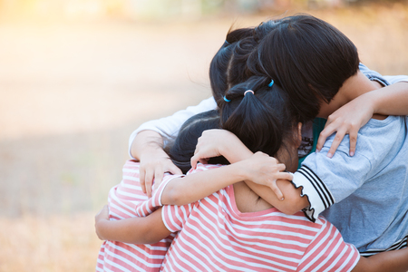Group of asian children hugging and playing together with love and fun in the park