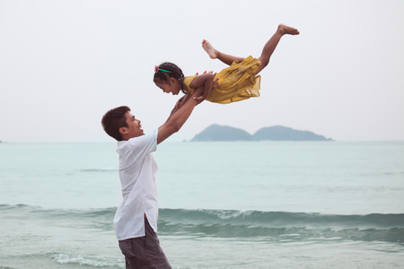 Asian father throwing his daughter up in the air and playing together in the sea with fun and love in summer vacation Stock Photo