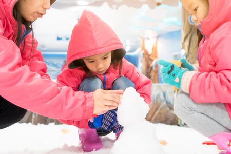 雪で遊ぶピンクのジャケットを着て、楽しさと初めて雪の土地で彼女の家族と雪だるまを成形するかわいいアジアの小さな女の子