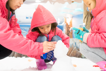 Cute asian little child girl wearing pink jacket playing with snow and molding snowman with her family in snow land in the first time with fun Stockfoto