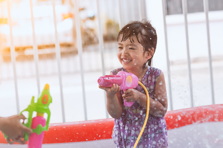 Happy asian little child girl having fun to play water with water gun and in Songkran festival Thailand Stock Photo
