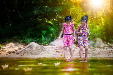 Two asian little child girls playing paper boat in the riverside together in summer time with fun and happiness