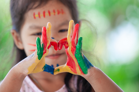 Child's hand with painted colorful watercolor make heart shape on green nature background Stock Photo