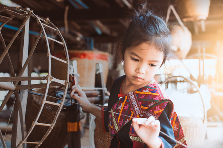 Cute asian child girl in Thai traditional dress using traditional wooden spinning wheel with fun and curious Standard-Bild - 101152977