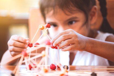 Cute asian child girl playing and creating with play dough and toothpick. Child concentrated with play dough building a molecule model. Stockfoto