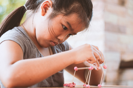 Cute asian child girl playing and creating with play dough and toothpick. Child concentrated with play dough building a molecule model. Stock Photo