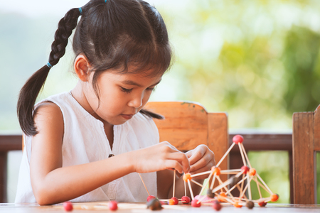 Cute asian child girl playing and creating with play dough and toothpick. Child concentrated with play dough building a molecule model. Banque d'images