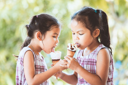 Two asian little child girls eating delicious icecream waffle cone together with fun and happiness 스톡 콘텐츠