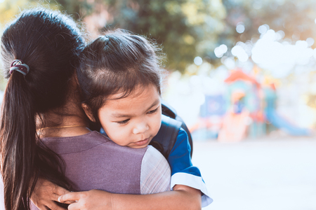 Back to school. Cute asian pupil girl with backpack hugging her mother with sadness in the playground before go to classroom in the school. Stok Fotoğraf