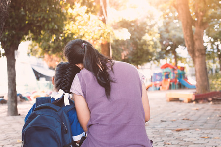 Back to school. Asian mother and daughter with backpack sitting together in the playground before go to classroom in the school. Фото со стока