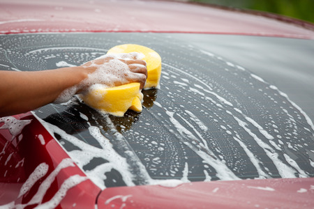 Man washing red car with sponge and soap Stock Photo