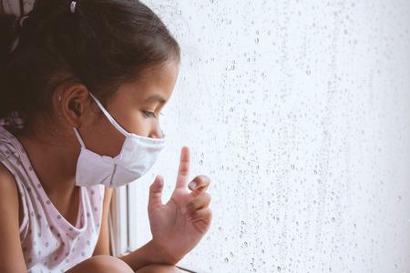 Niña asiática enferma usa máscara protectora mirando hacia afuera a través de la ventana en el día lluvioso Foto de archivo