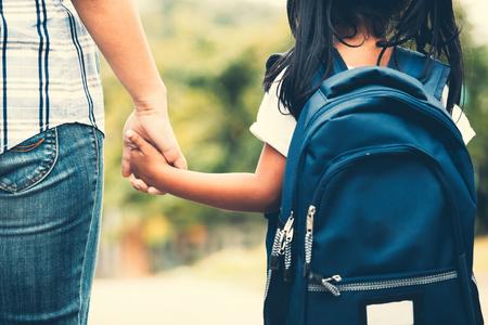 Terug naar school. Leuk Aziatisch leerlingmeisje dat met rugzak haar moederhand houdt en naar school gaat in vintage kleurtoon
