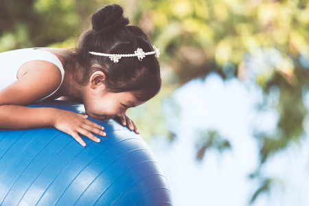 Cute asian child girl doing stretching exercise on fitness ball