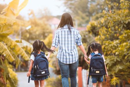 Zurück zur Schule. Asiatisches Mutter- und Tochterschülermädchen mit dem Rucksack, der Hand hält und zur Schule zusammen im Weinlesefarbton geht