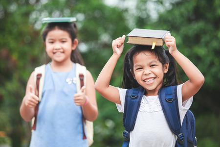 Back to school. Cute asian child girl with school bag and her sister put a book on head together with fun