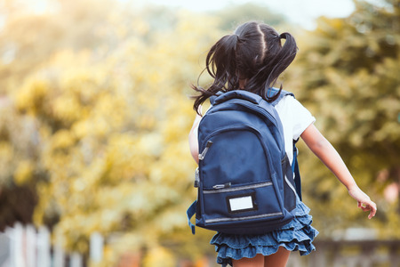 Back to school. Cute asian child girl with backpack running and going to school with fun Stock Photo