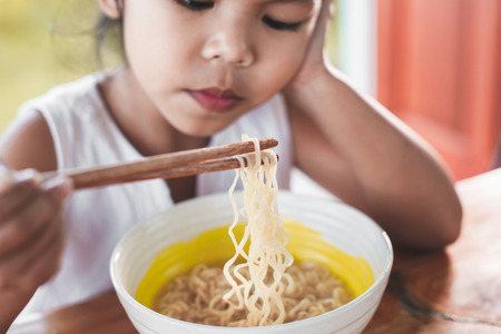 Cute asian child girl bored to eat Instant noodles for her meal