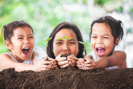 Happy family mother and daughter having fun to holding young tree in hands for planting in black soil together