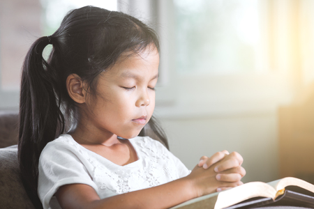 Cute asian little child girl closed her eyes and folded her hand in prayer on a Holy Bible for faith concept