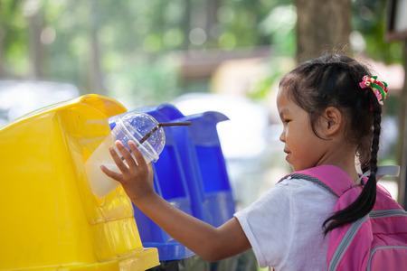 Ragazza asiatica sveglia del bambino che getta il vetro di plastica nel riciclaggio del bidone della spazzatura al parco pubblico Archivio Fotografico