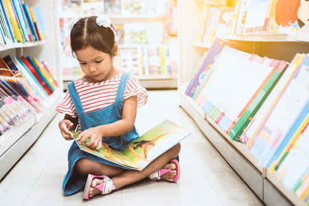 Cute asian child girl select book and reading a book in bookstore in supermarket Stock Photo