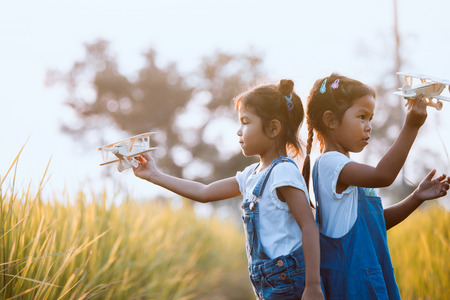 Two cute asian child girls playing with toy wooden airplane in the field at sunset time together with fun