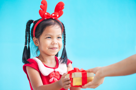 Parent giving Christmas gift to cute asian child girl on Christmas celebration