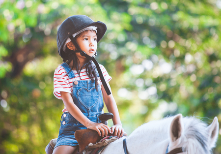 Cute asian child girl riding a horse in the farm with fun