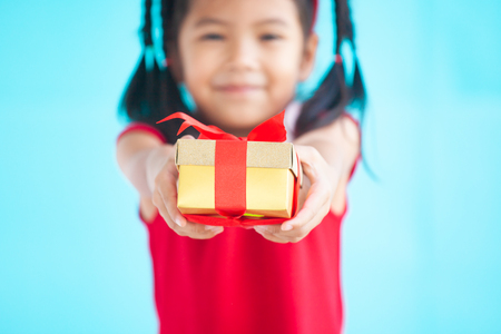 Cute asian child girl holding beautiful gift in hand on Christmas celebration