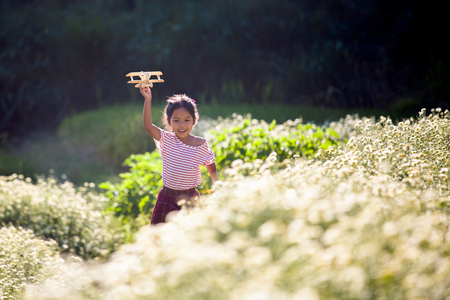 Cute asian child girl running and playing with toy wooden airplane in the flower field at sunset time with fun