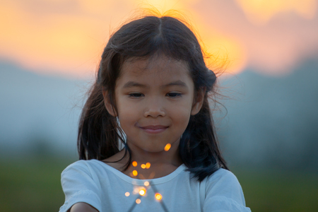 Cute asian child girl are playing with fire sparklers on the festival in the rice field at sunset time Stock Photo