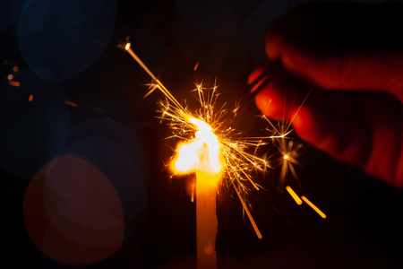 family party woman holding and playing with fire sparklers on the festival Stock Photo