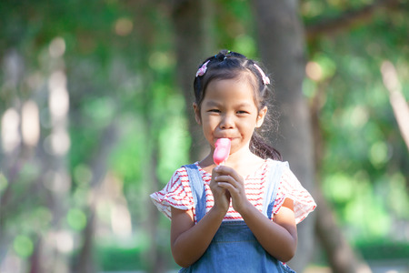 Cute asian child girl eating ice-cream in the park