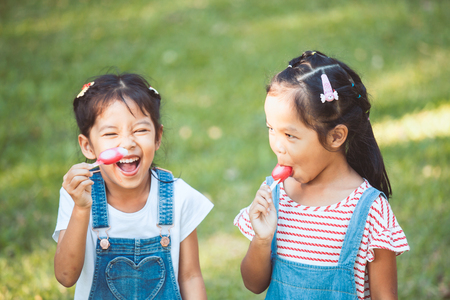Two cute asian child girls eating ice-cream together in the park