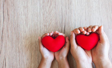 Red heart in child hands and parent hands on wooden table background with love and harmony Imagens