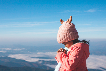 Cute asian child girl wearing sweater and warm hat making folded hands in prayer in beautiful mist and mountain background in winter