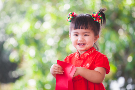 Cute asian little child girl smiling and getting money in red envelope and wishing you a happy in Chinese New Year