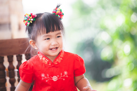Happy cute asian little child girl in chinese tradition dress smiling  and wishing you a happy in Chinese New Year Banco de Imagens