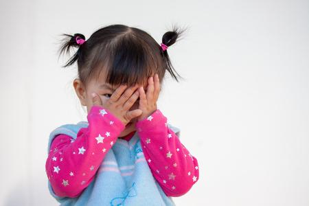 Jolie petite fille asiatique fermant son visage et jouant à cache-cache ou à cache-cache avec plaisir