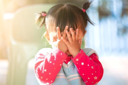Bambina asiatica carina che chiude la faccia e gioca a nascondino o a nascondino con divertimento Archivio Fotografico