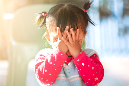 Cute asian baby girl closing her face and playing peekaboo or hide and seek with fun 免版税图像 - 121596021