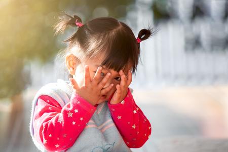 귀여운 아시아 아기 소녀가 얼굴을 가린 채 엿보기를 하거나 숨바꼭질을 하고 재미있다.