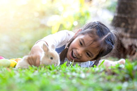 Cute asian child girl playing with little bunny rabbit with love and tenderness in the meadow