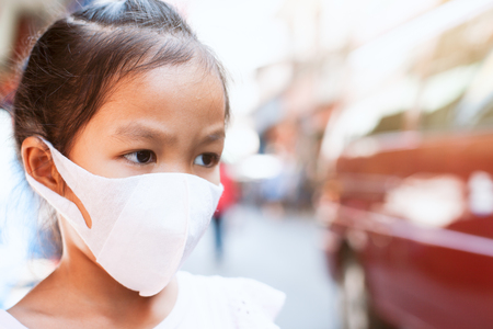 Cute asian child girl wearing protection mask to against air smog pollution with PM 2.5 in the city 免版税图像